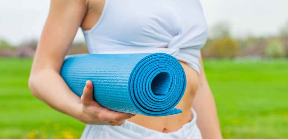woman standing outside and holding blue yoga mat