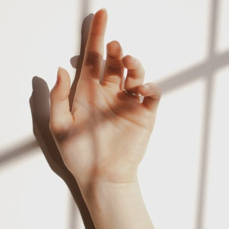 Female hand against wall with shadow